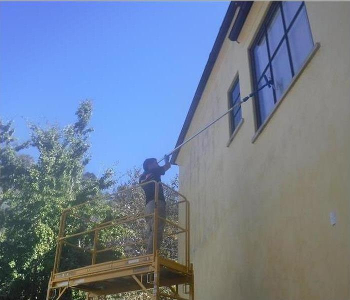Technician on top of a scaffold cleaning the windows.