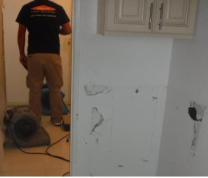 Photo of a damaged wall due to water damage with a technician facing his back.
